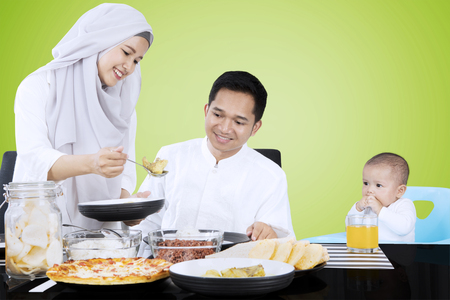 Muslim female serves food for family in dining table while her husband and child sit with green background