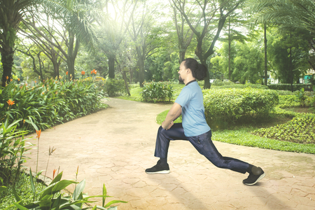 Portrait of Afro man with curly hair, doing workout and stretching his legs in the park while wearing sportswear Stock Photo