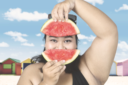 Obese woman wearing swimsuit with slice of fresh watermelon near the cottage
