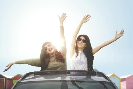 Two happy women wearing sunglasses, enjoying freedom on car sunroof near the cottage