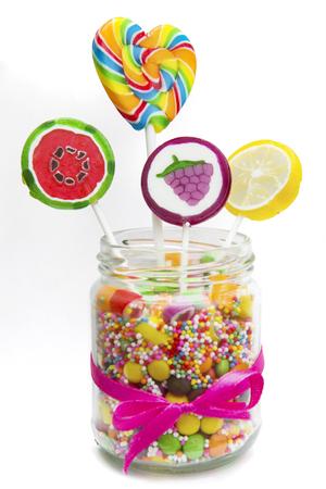 Geassorteerde fruitsuikergoed en lollys in glaskruik met roze die lint, op witte achtergrond wordt geïsoleerd Stockfoto