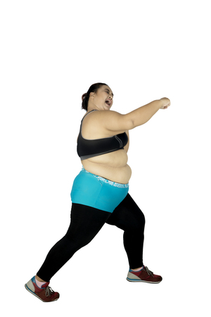Portrait of fat woman wearing sportswear while exercising with punching style, isolated on white background Stock Photo