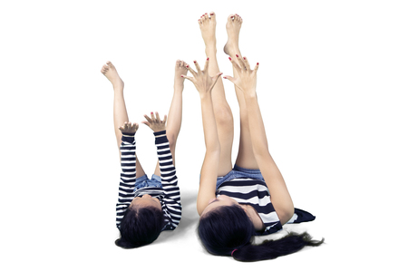 Image of young mother lying on the floor with her daughter while exercising together in the studio