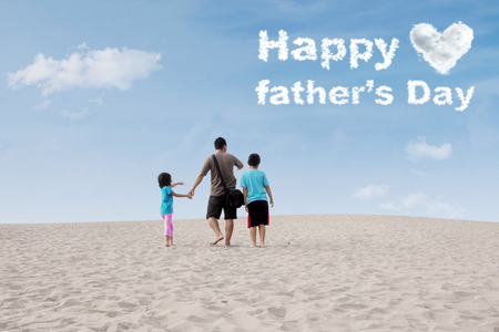 footprints in sand: Rear view of a young father and his children walking on the sea of sand while looking at a text Happy Fathers Day on the sky