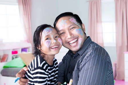 father and daughter: Little girl and her father with painted face while playing with crayons and laughing together