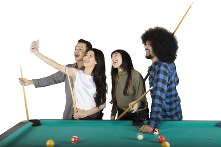 Group of happy multiracial people taking a selfie photo together next to pool table, isolated on white background