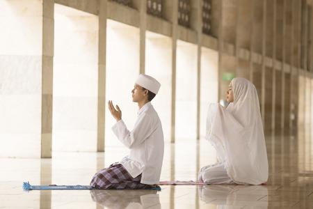 Moslim man en vrouw bidden samen voor Allah in de moskee Stockfoto