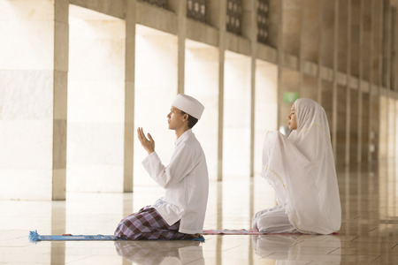 Muslim man and woman praying for Allah in the mosque together