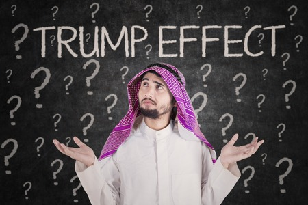 skepticism: Arabian businessman looks confused with Trump Effect word and question marks on the background