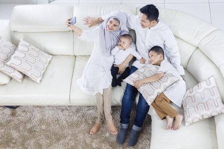 Vista superior de la familia musulmana que toma la foto del selfie mientras que sonríe y se sienta en el sofá junto