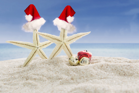 Christmas vacation concept. Couple of starfishes in Santa Claus hats on the white sand beach with christmas bells