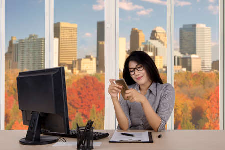work: Portrait of a beautiful businesswoman reading messages on her smartphone while working in the office