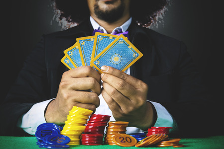 gambler: Businessman playing poker cards in a gambling with stack of chip on the table