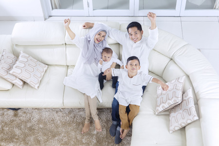 Top view of muslim family expressing their happiness while sitting on the sofa together
