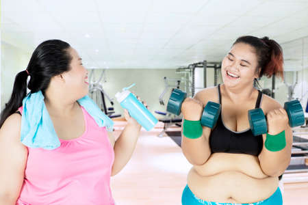 Fat woman drinking water on a bottle while speaking with her friend doing training in the gym center