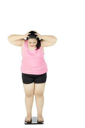 oversize: Diet concept. Full length of frustrated overweight woman standing on scale and looks unhappy, isolated on white background