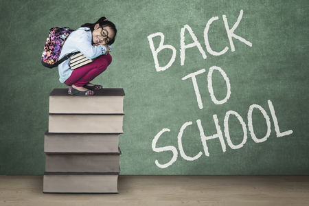 rucksacks: Concept of Back to School. Female elementary school student squat on a pile of books with text of Back to School on the chalkboard