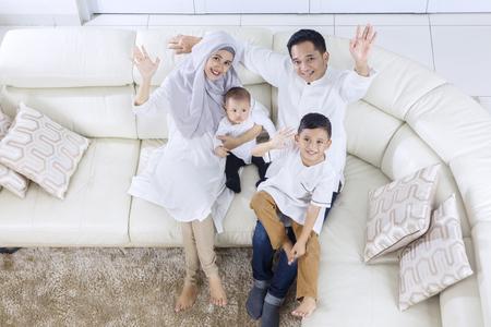 Angle élevé de famille musulmane levant les mains tout en souriant et assis sur le canapé Banque d'images - 80148689