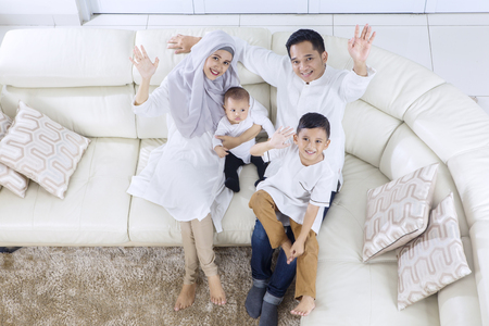 High angle of muslim family raising hands while smiling and sitting on the sofa Stockfoto
