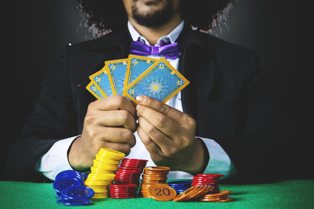 Picture of Afro man with curly hair, holding poker cards in a gambling with chip on the table