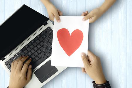 Beeld van jonge vader die laptop met behulp van terwijl het houden van een groetkaart van zijn zoon, concept vaderdag