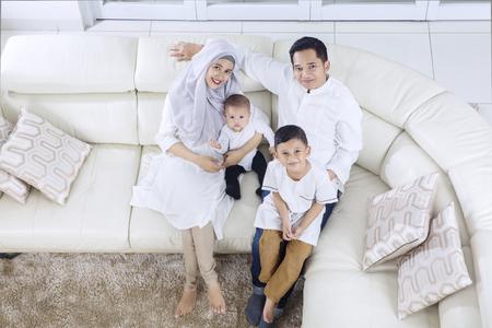 Hoogste mening van moslimouders en kinderen die op de bank zitten terwijl thuis het glimlachen samen
