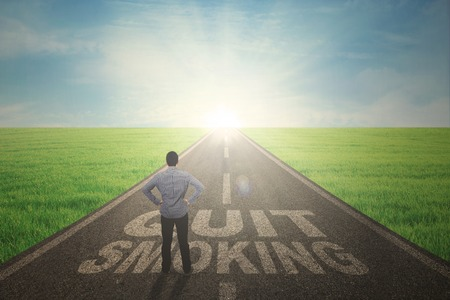 Back view of young male standing on a text of quit smoking while looking at the sunbeam on the end road photo
