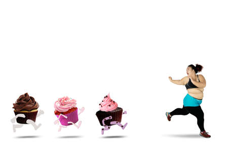 fearful: Diet concept. Overweight woman refusing to eat sweet foods to lose weight and run away from cupcakes, isolated on white background