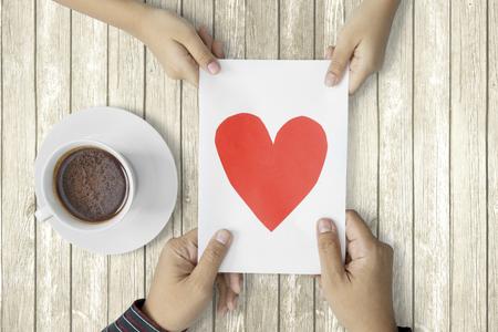 bebes niñas: Vista superior de la pequeña hija que da la tarjeta de felicitación al padre con una taza de café en la tabla de madera