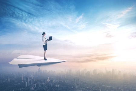 Young businesswoman standing on a paper aeroplane while using a laptop computer and flying above a city