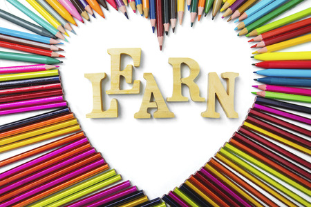 sharp: Education concept. Top view of color pencils shaped heart symbol with Learn text