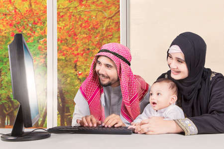 Image of cheerful Arabian family looking at a light screen on the monitor while using computer together with autumn background on the window photo