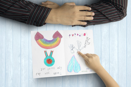 first day: Fathers Day. Top view of child hand and dad pointing at a greeting card with family picture, love symbol, and handwritten on desk