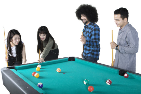 Multicultural group of young friends playing billiard together, isolated on white background