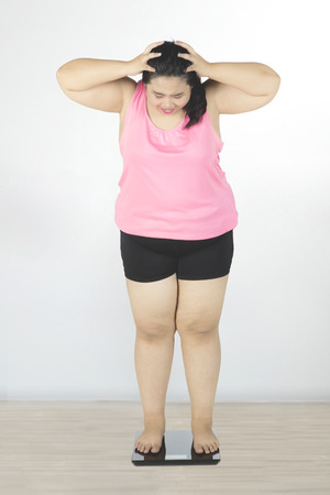 oversize: Obese woman holding her head and depressed after fail to lose weight while looking at weight scale