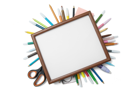 High angle view of a blank frame over school supplies, isolated on white background