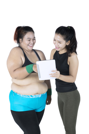 Female trainer showing something on digital tablet to fat woman, isolated on white background Stock Photo