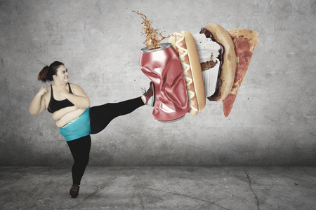 Diet Concept. Overweight woman kicks a can of soft drink and junk foods while wearing sportswear. Isolated on white background Archivio Fotografico