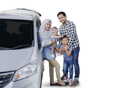 Image of happy Muslim family standing beside a car while smiling at the camera, isolated on white background
