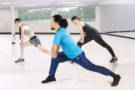 Multi ethnic of young friends doing stretching exercise together in the fitness center Stock Photo