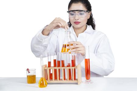 investigando: Retrato de mujer india haciendo la investigación con líquido en el tubo de ensayo, aislado sobre fondo blanco
