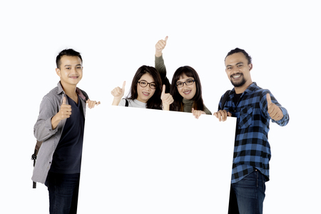 spolužák: Group of multiethnic college students showing thumbs up while holding an empty banner, isolated on white background