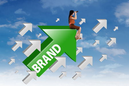 Businesswoman sitting on the upward arrow with brand word and looking at the sky through binocular Stock Photo