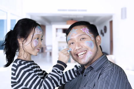 Picture of young father and his daughter playing with a crayon while drawing their face at home