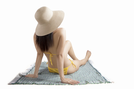 Rear view of young woman sitting on the mat while enjoying summertime with bikini, isolated on white background photo