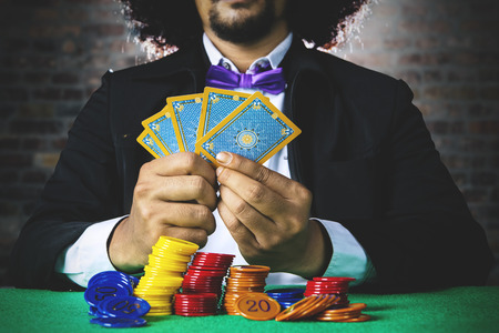 Male gambler wearing business suit and holding five poker cards with chip on the table in the casino
