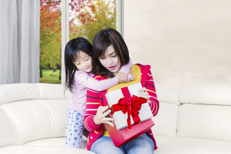 Young Asian woman opens a gift box with her daughter while sitting on the couch at home with autumn background on the window photo