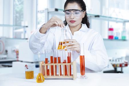 investigando: Mujer científica con gafas y haciendo la investigación de la bioquímica con líquido químico rojo y naranja en el laboratorio