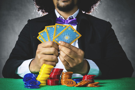 frizzy: Photo of a male gambler playing poker cards while wearing formal suit with chip on the table in the casino