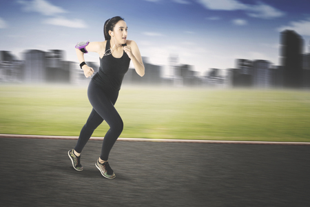 Young arabian woman wearing sportswear, running while listening music on earphone on the road Stock Photo